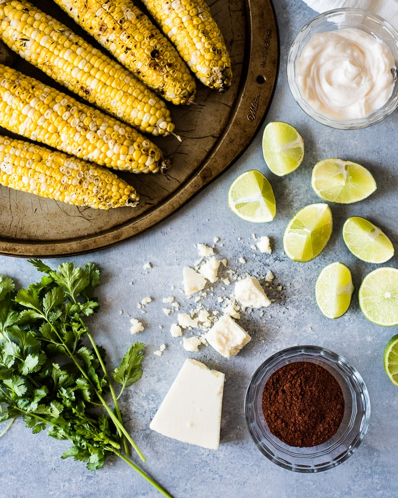 Crumbled cotija cheese on a table with other ingredients used to make Mexican street corn.