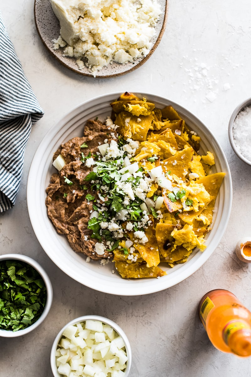 A white bowl filled with migas and refried beans topped with cilantro, onions and queso fresco.