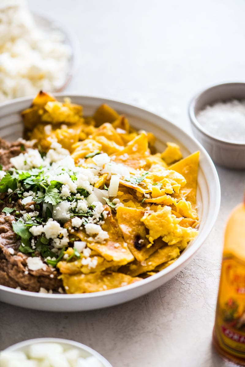 Migas recipe made from fried corn tortillas and eggs in a bowl with refried beans topped with queso fresco.