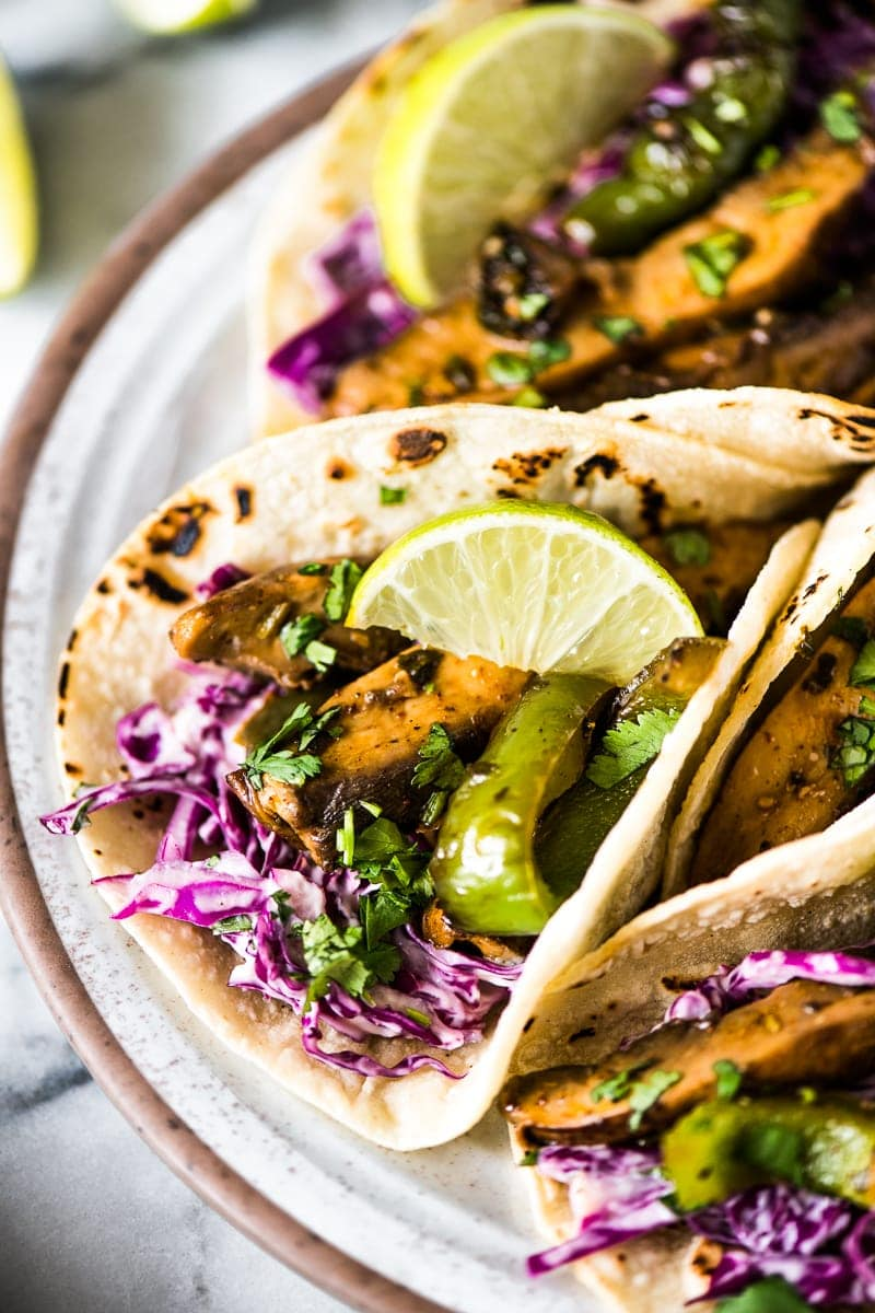 Mushroom tacos filled with marinated portabella mushrooms, bell peppers and red cabbage slaw