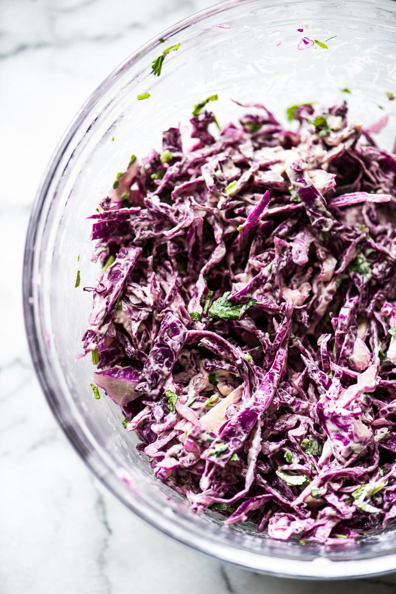 Shredded red cabbage in a large bowl with mayo and chopped cilantro for vegetarian tacos topping