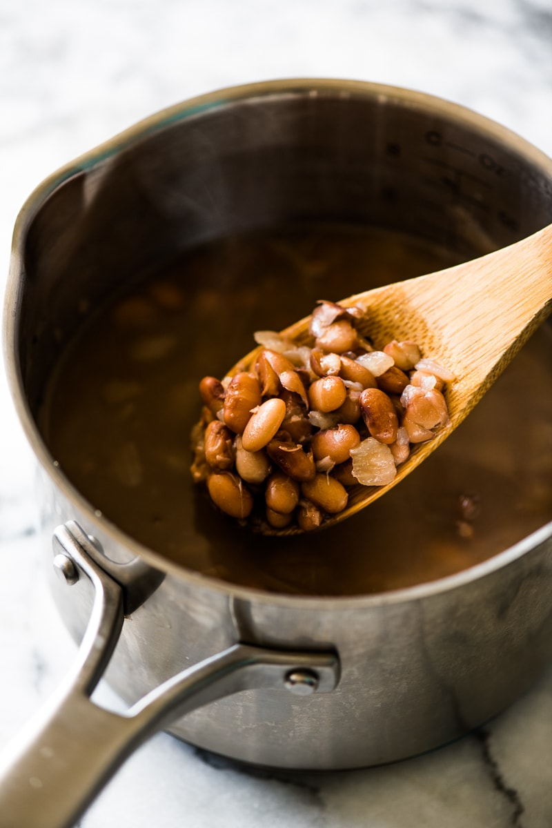 Cooked pinto beans on a wooden spoon in a stainless steel pot.