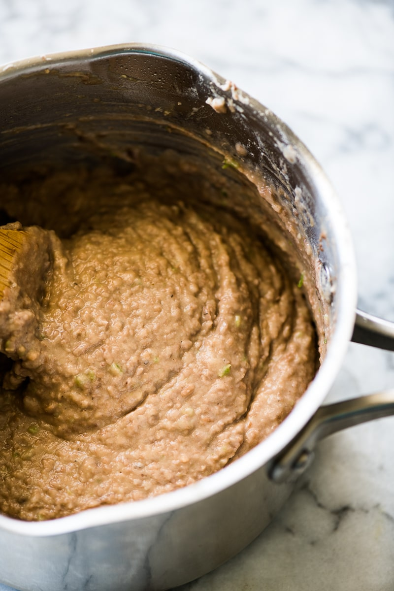 Creamy refried beans in a stainless steel pot