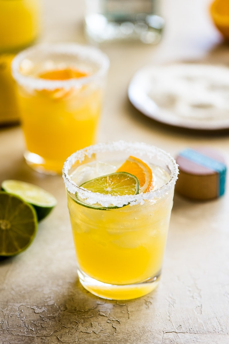 Skinny margarita cocktail glass garnished with sliced lime and orange.