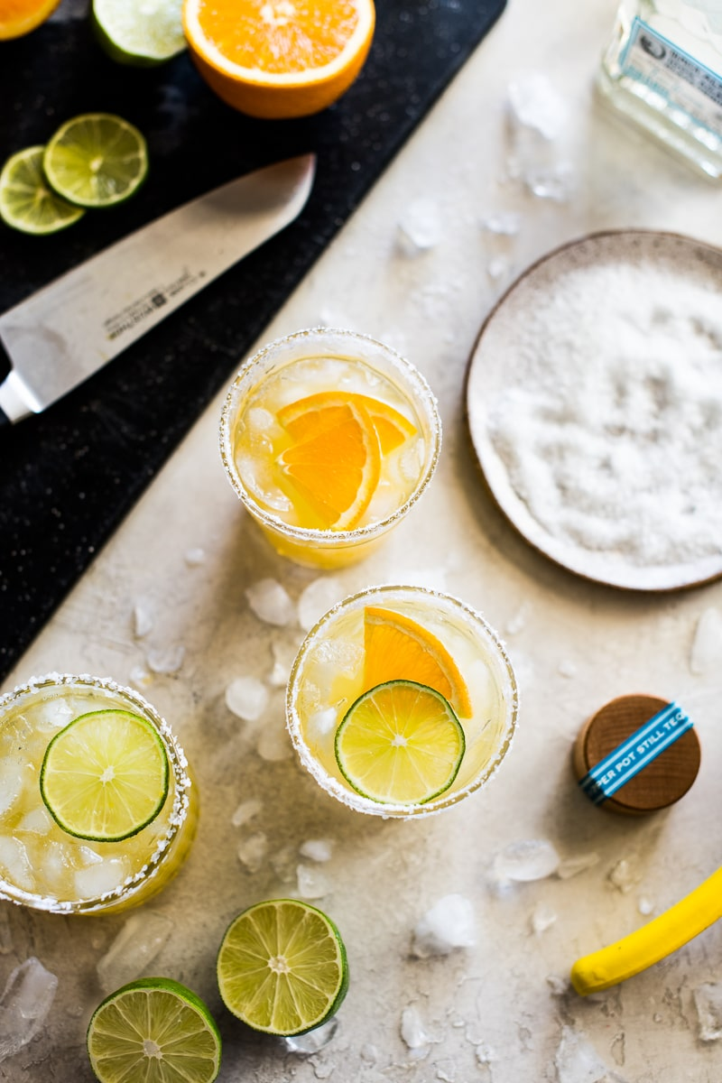 Skinny Margaritas on a table with salt, limes, tequila, oranges and ice cubes.