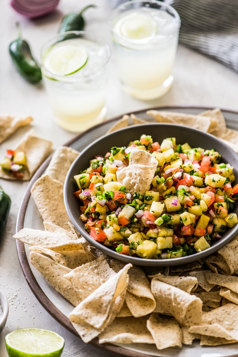 Pineapple salsa in a bowl with a tortilla chip scooping some out.