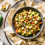 Pineapple salsa in a bowl surrounded by tortilla chips.