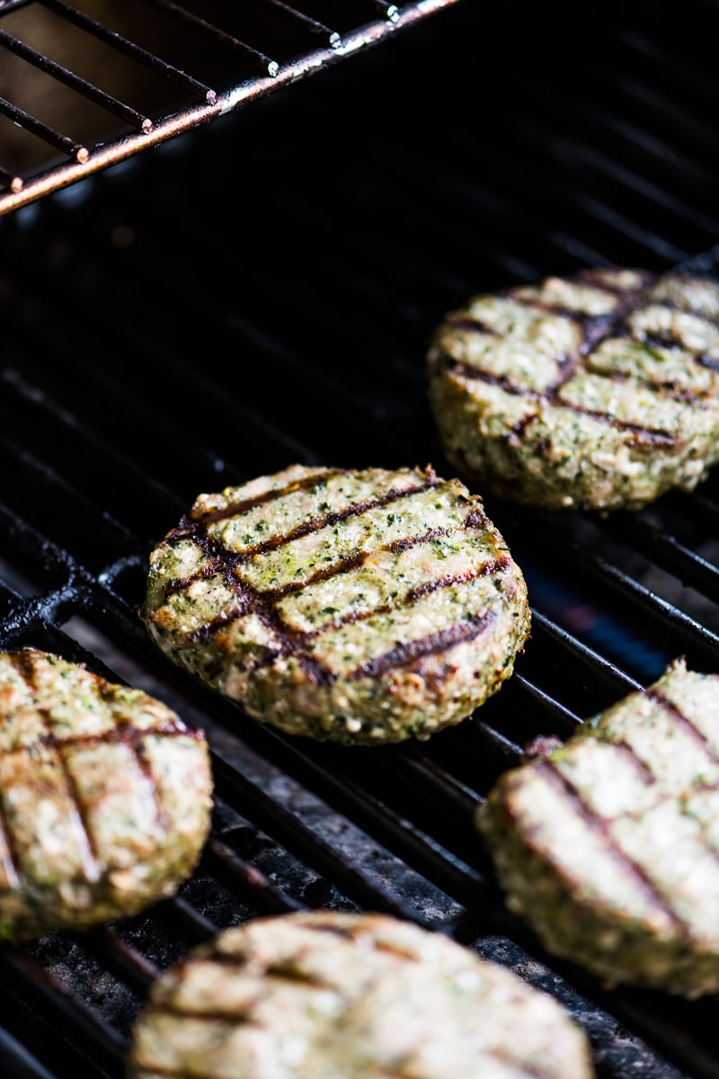 Honeysuckle White Spinach and kale turkey burgers being cooked on a grill.