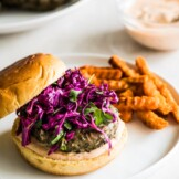 A grilled turkey burger sitting on a hamburger bun topped with chipotle lime mayo and a red cabbage slaw.