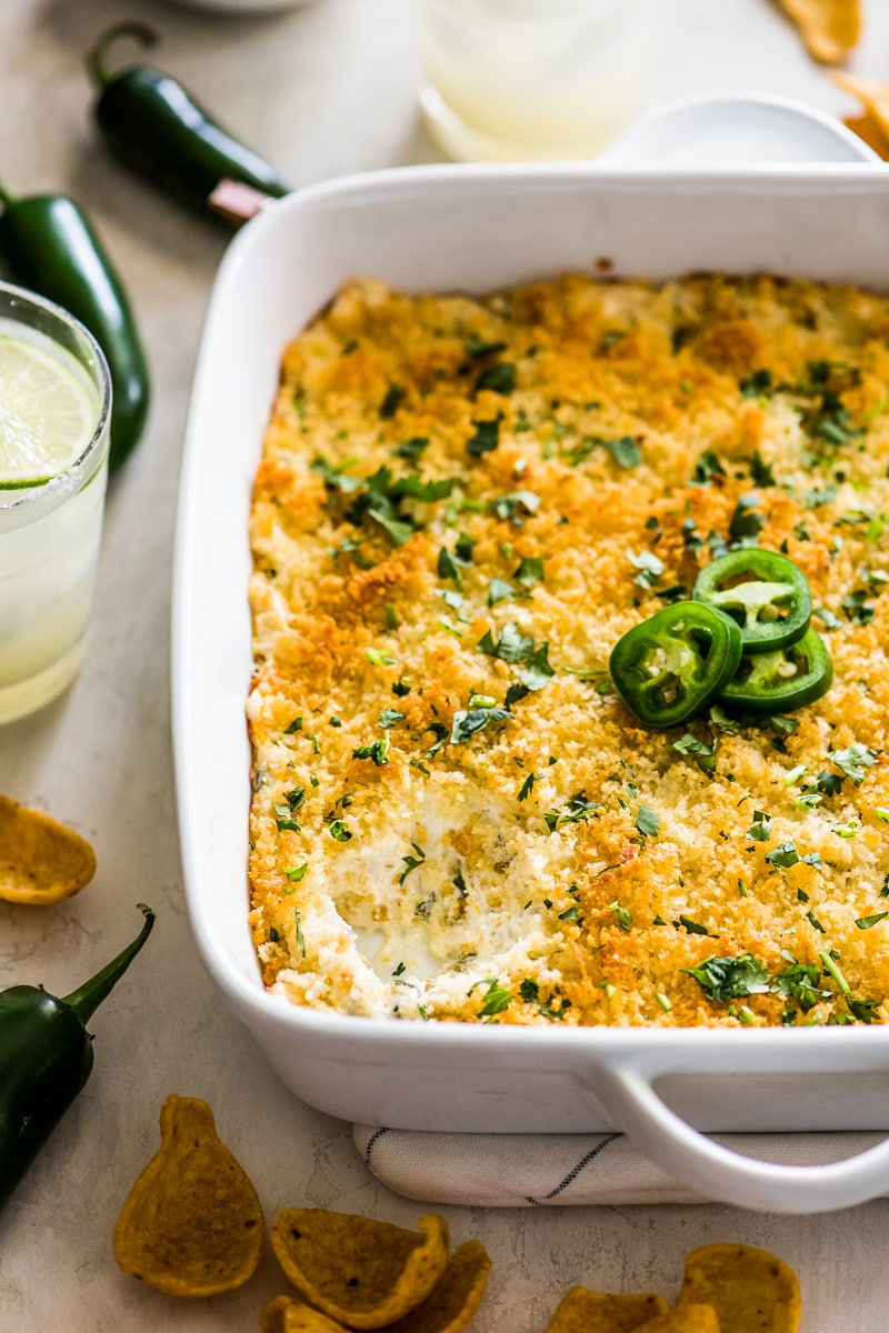 Jalapeno Popper Dip in a white square baking dish with a a scoop taken out so you can see the cream cheese mixture.
