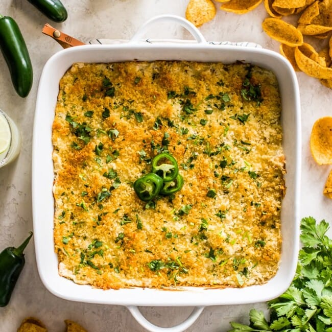Jalapeno Popper Dip in a white square baking dish surrounded by corn chips, jalapenos, cilantro and margaritas.