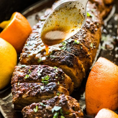 A spoon pouring citrus juices over roasted pork tenderloin in a black cast iron skillet.