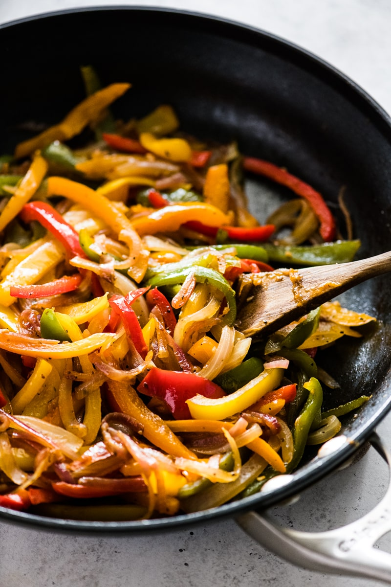 Sauteed peppers and onions in a black nonstick skillet.