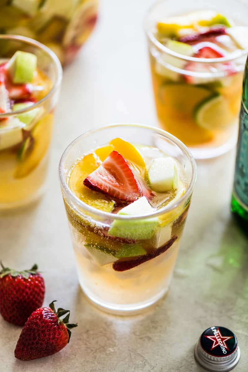White wine sangria in a clear glass topped with sliced strawberries and summer fruit.