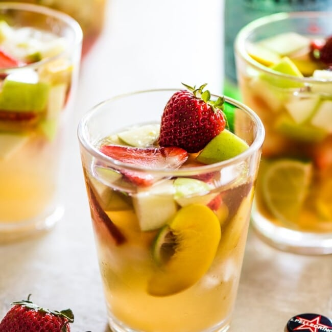 White sangria in a glass topped with summer fruit.