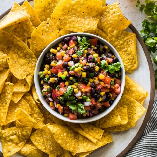 Black Bean and Corn Salsa in a white bowl surrounded by yellow tortilla chips.
