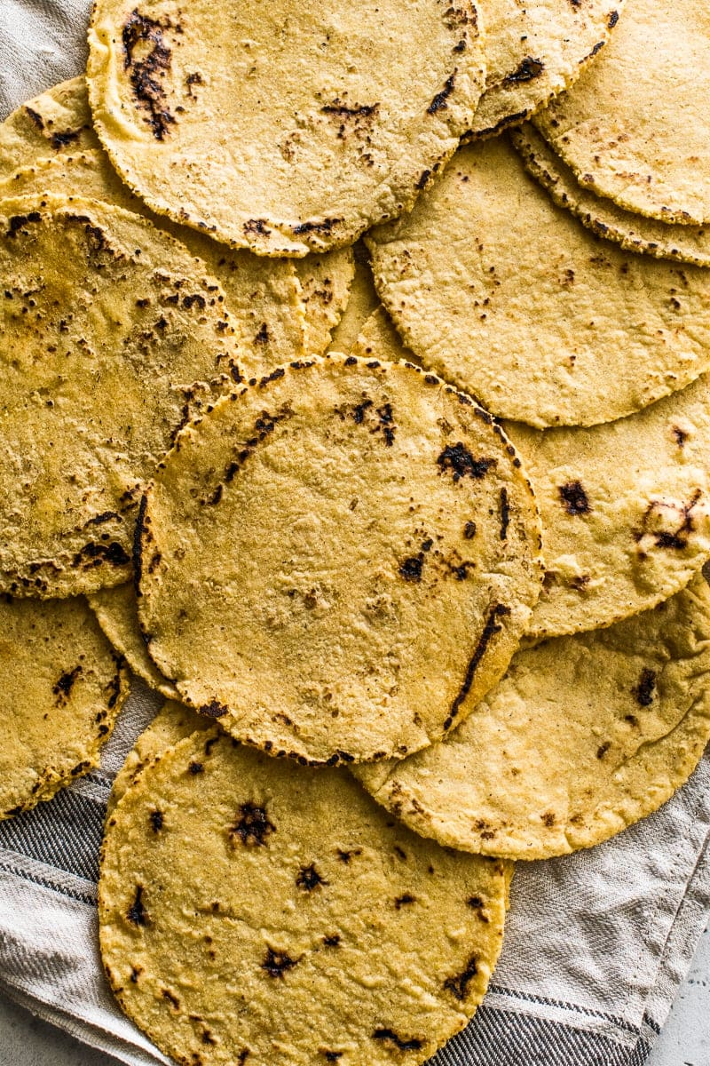 Cooked corn tortillas spread out on a clean kitchen towel.
