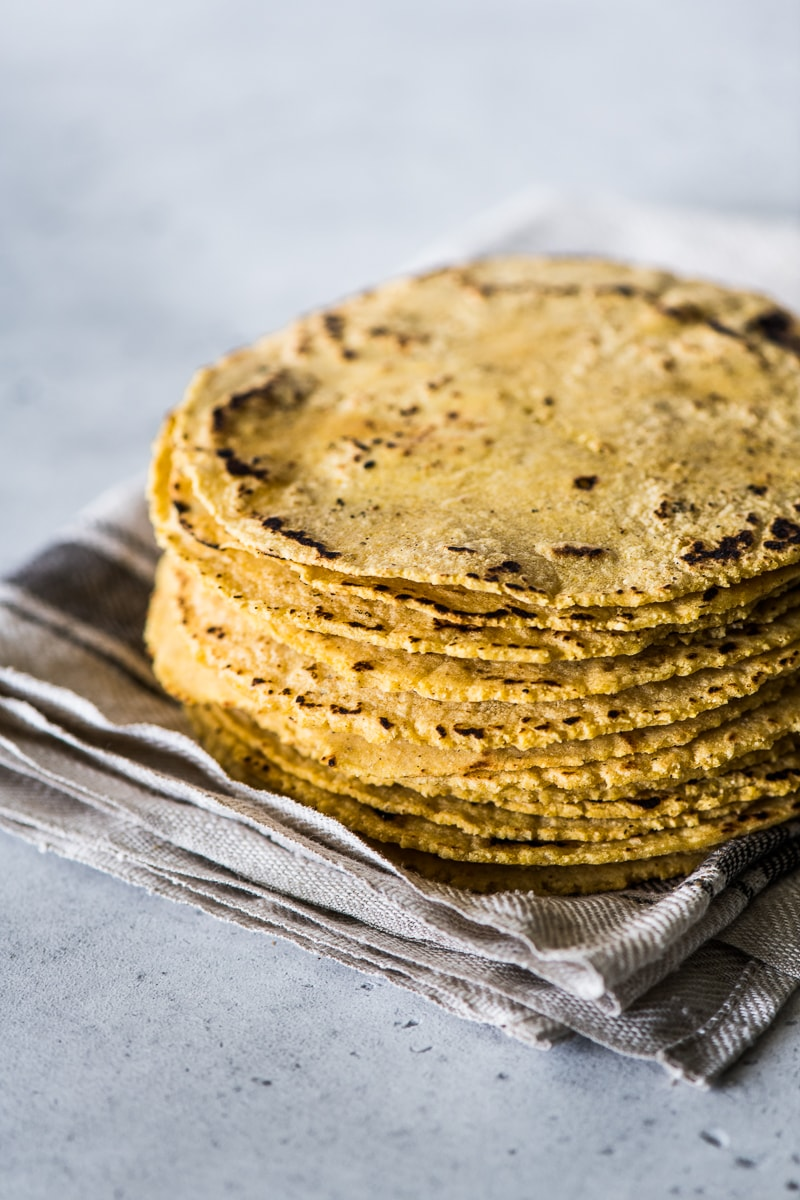 A stack of corn tortillas on a kitchen towel.