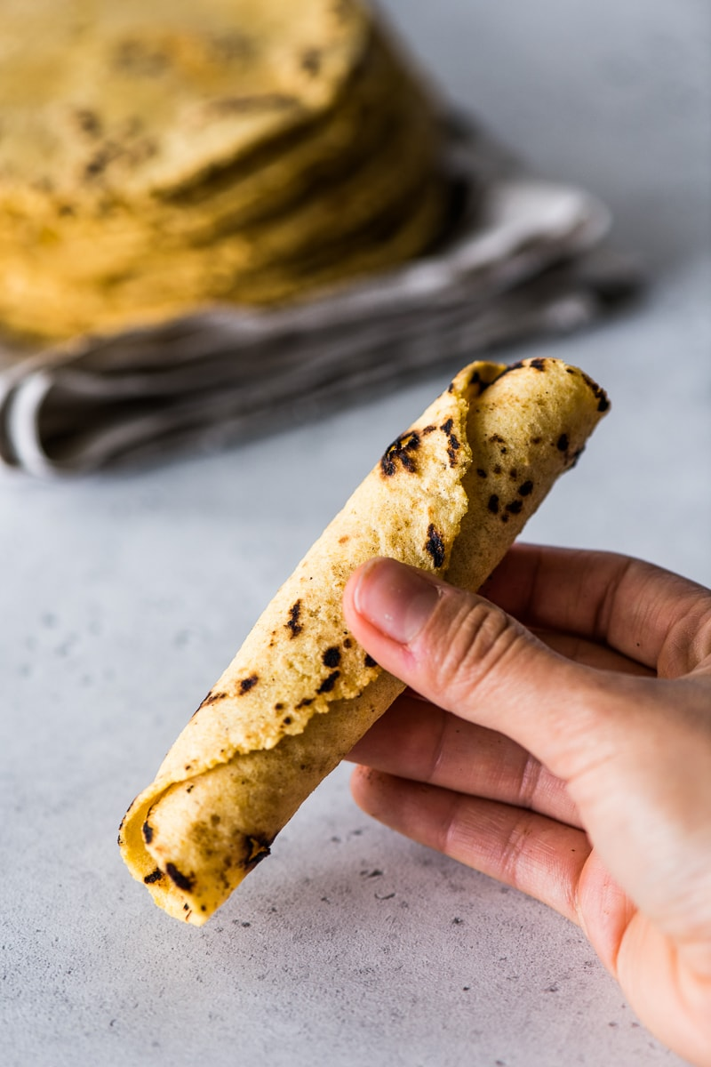 Rolled corn tortilla being held in a hand.