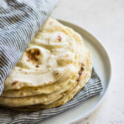 Flour tortillas in between a striped kitchen towel on a white plate.