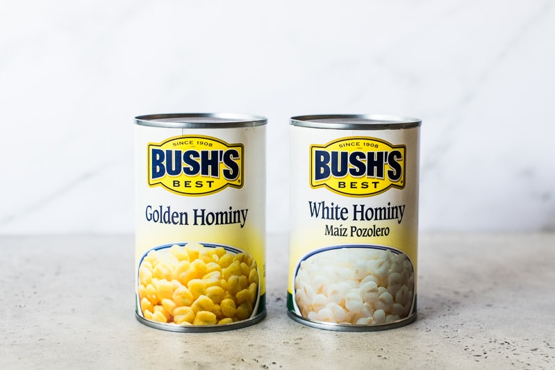 Two cans of different types of hominy. One is golden hominy and one is white hominy.
