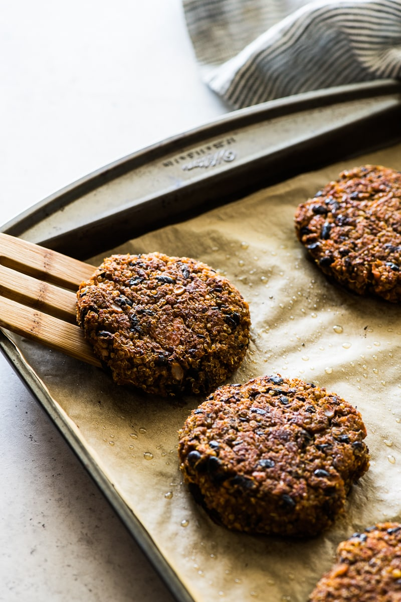 Cooked black bean burgers on a baking sheet lined with brown parchment paper.