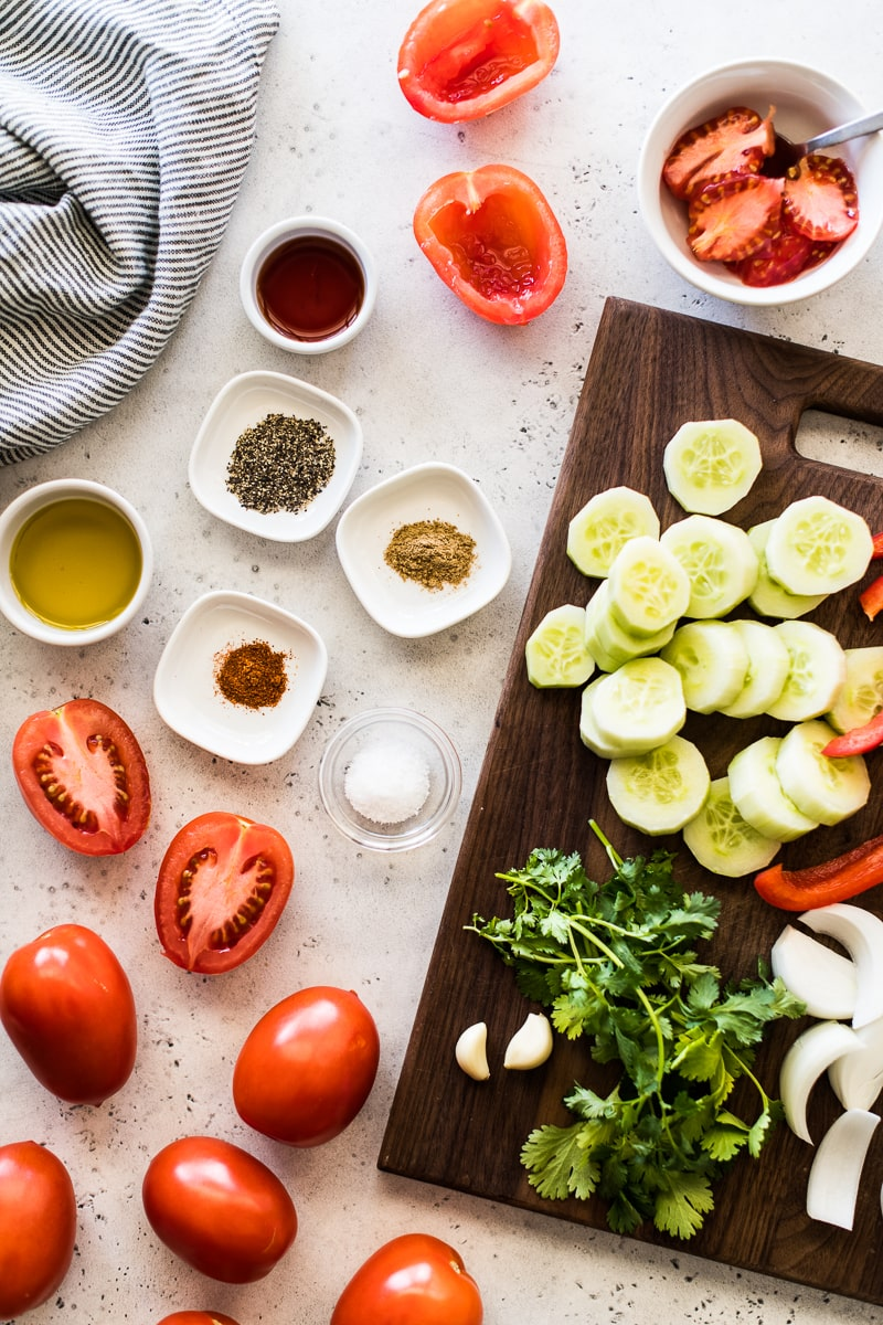 Ingredients for gazpacho on a white and blue table. Includes tomatoes, cucumbers, spices, olive oil, garlic, onions, red bell peppers and red wine vinegar.