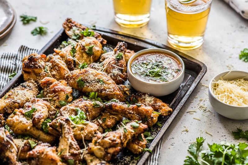 Grilled chicken wings on a serving tray with a side of garlic parmesan sauce.