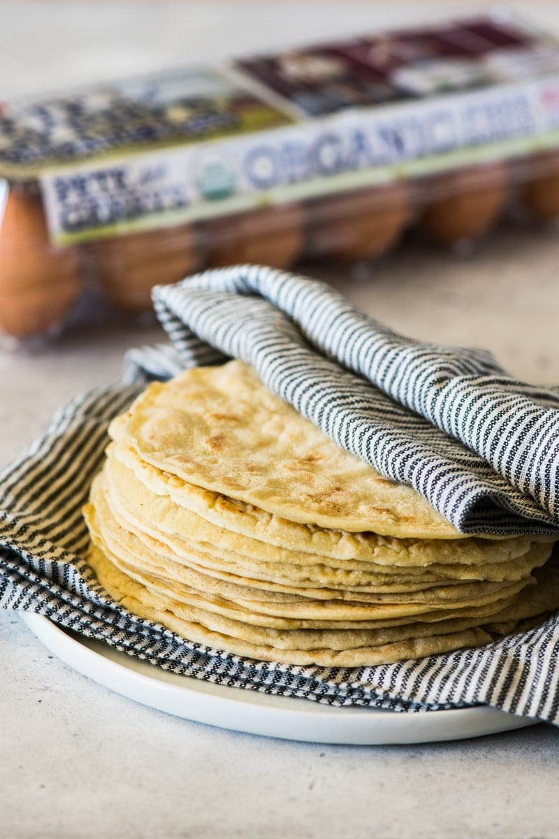 A stack of paleo tortillas covered with a clean kitchen towel.