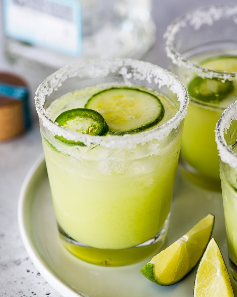 Cucumber margaritas in a glass rimmed with salt.