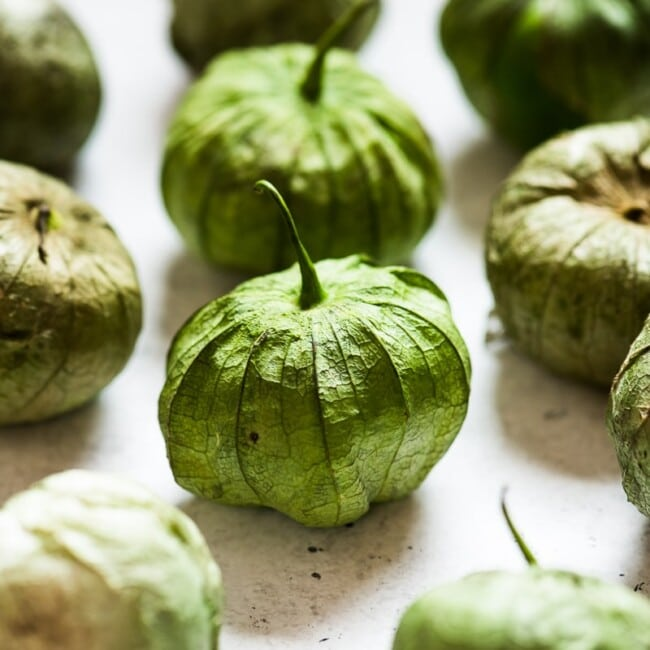 Tomatillos on a white table.