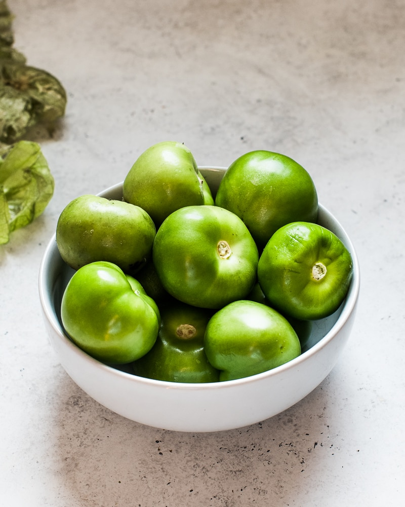 Green tomatillos in a white bowl with the skin and husk removed.