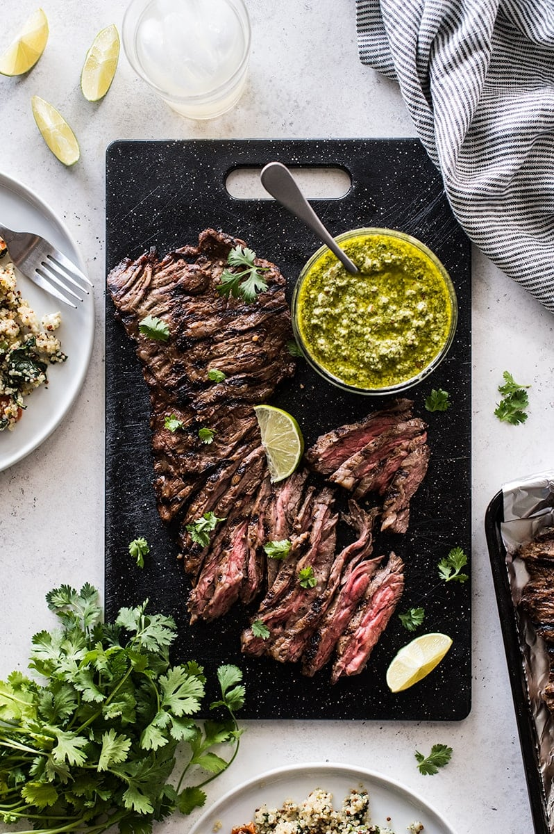 Thinly sliced grilled skirt steak on a cutting board topped with cilantro pesto.