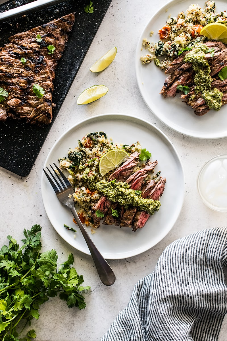 Grilled skirt steak slices on a plate of quinoa topped with cilantro pesto