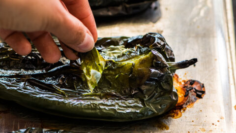 Pulling the skin off of roasted poblano peppers
