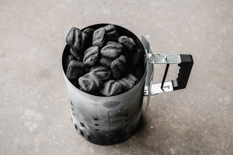 Charcoal briquettes in a chimney starter.
