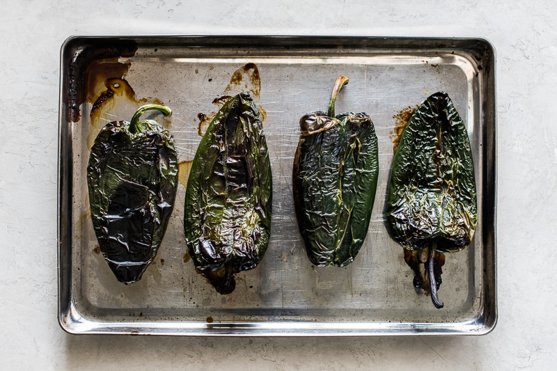 Roasted poblano peppers on a large baking sheet.