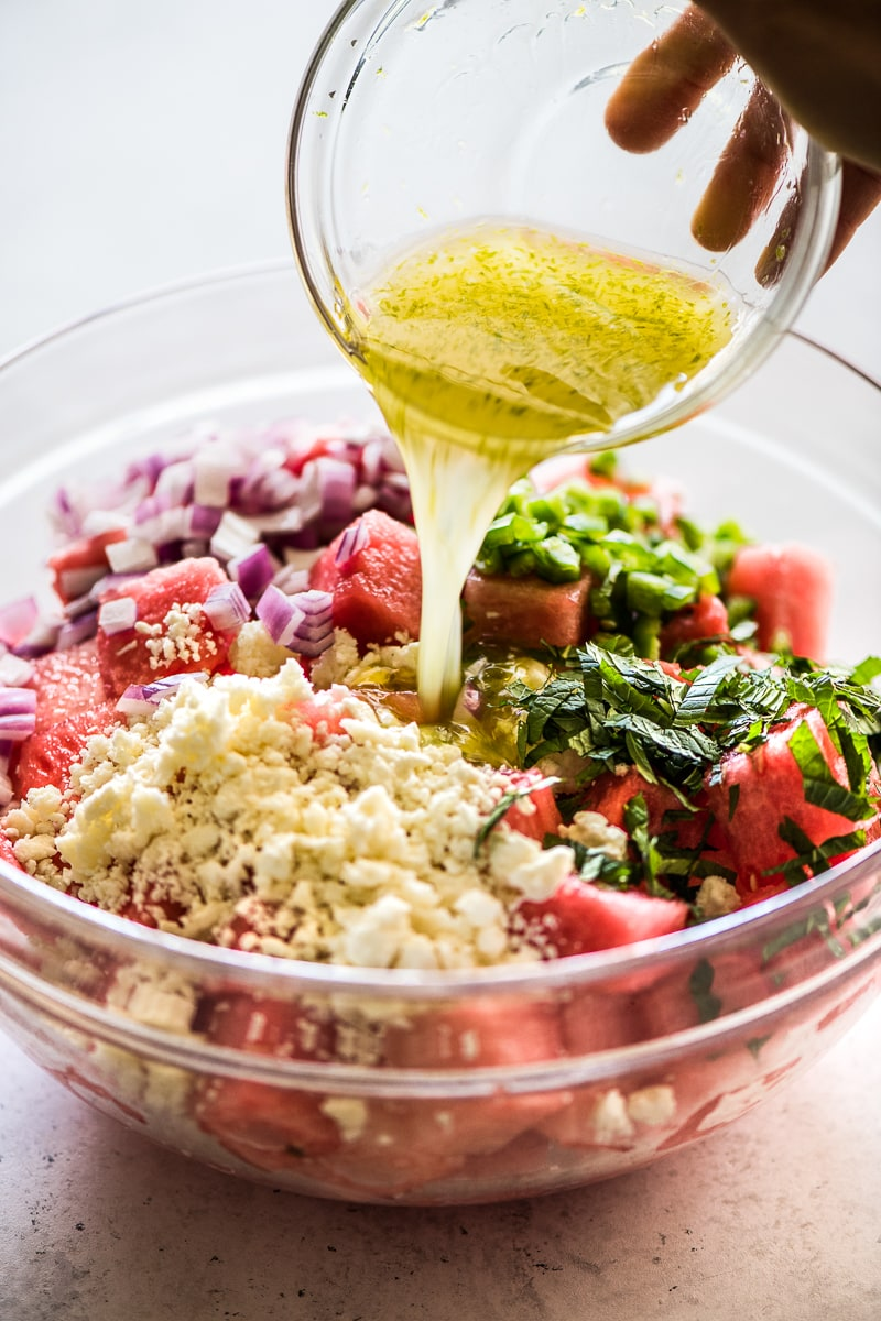 Lime dressing being poured in a bowl of watermelon salad.