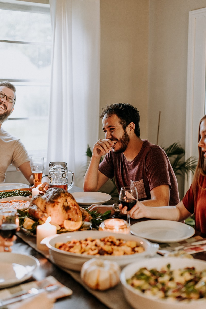 People laughing at a dining room table filled with Thanksgiving food in celebration of Friendsgiving.