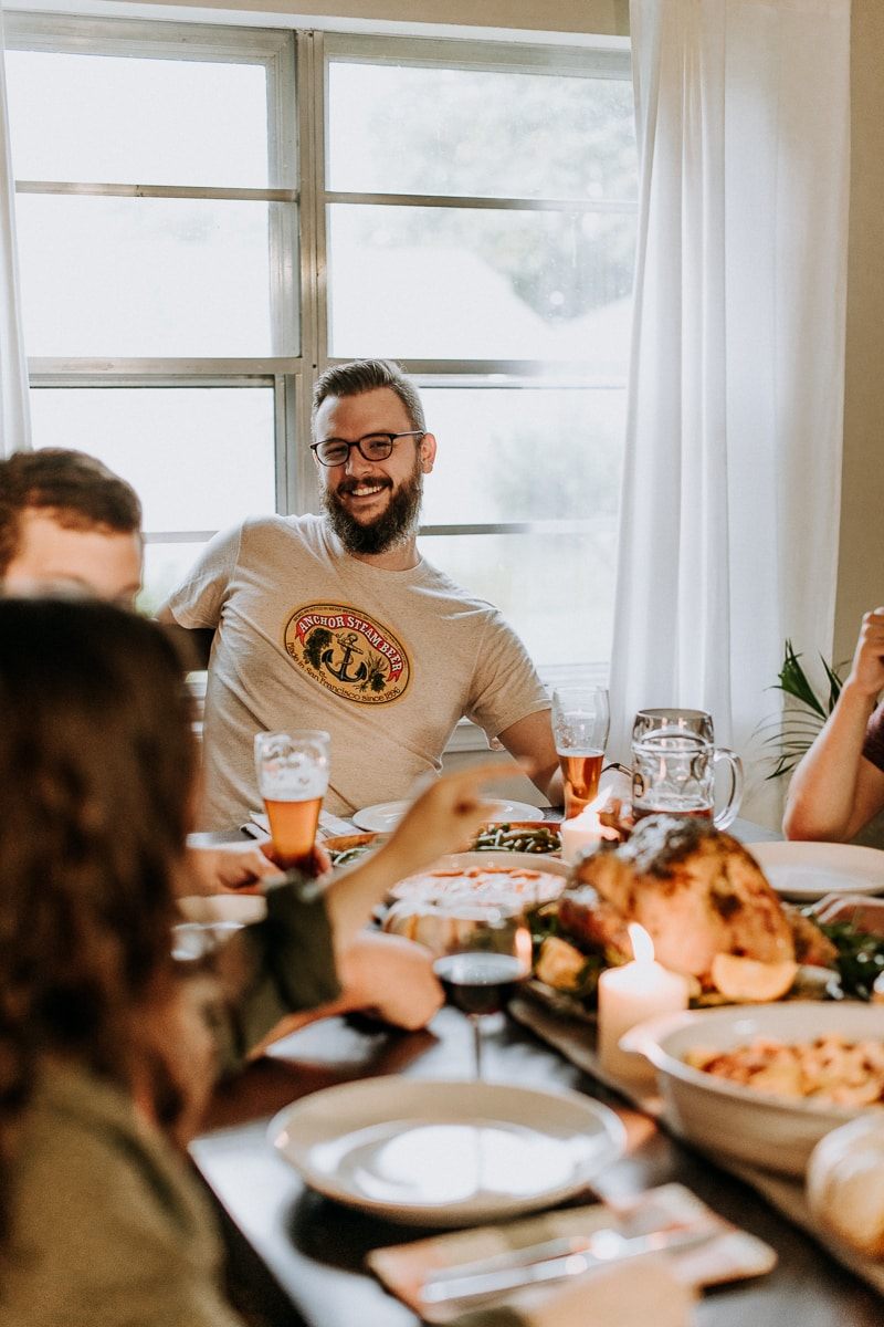 A group of people enjoying themselves at a table set for a Friendsgiving celebration.