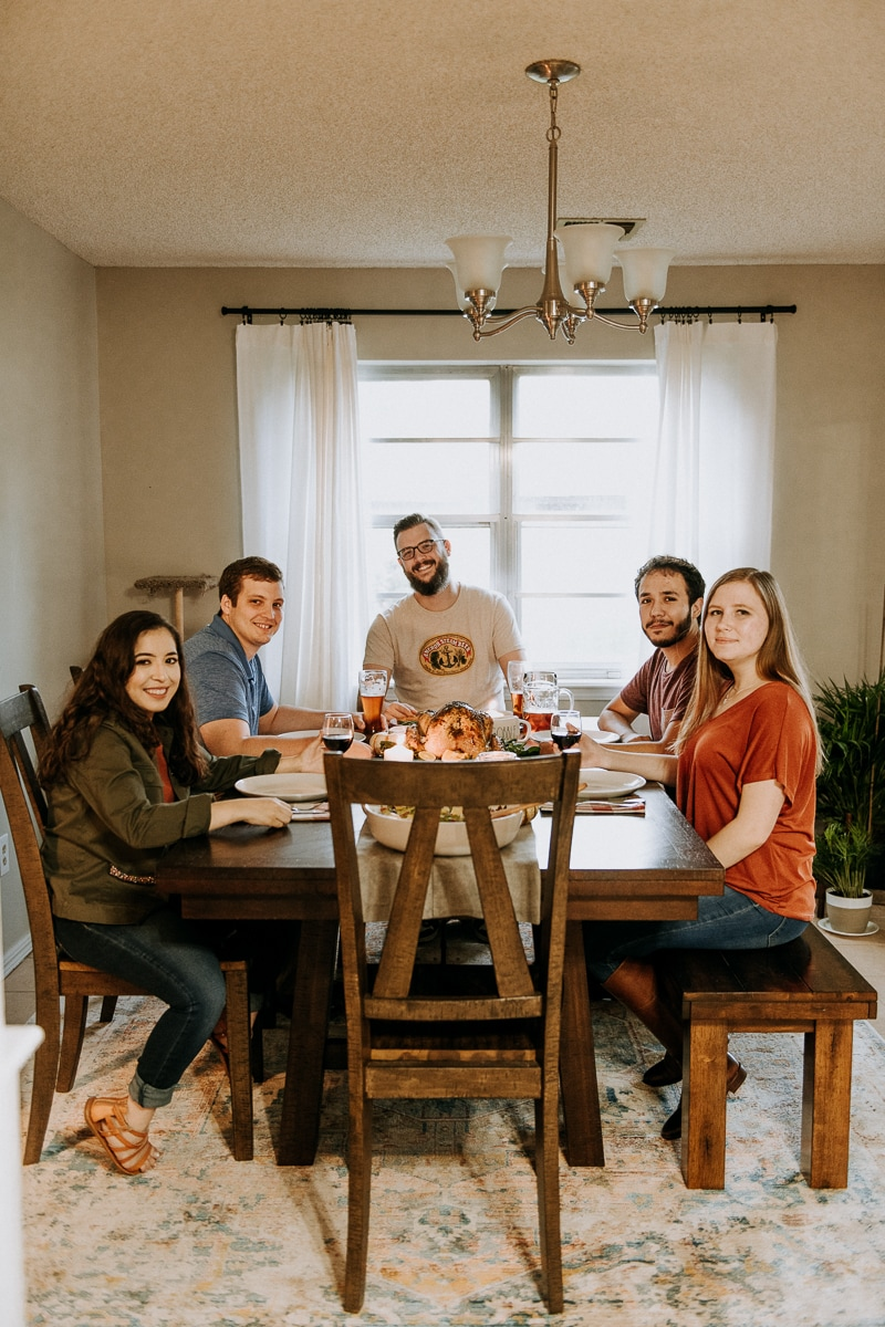 Friends smiling around the dinner table for Friendsgiving