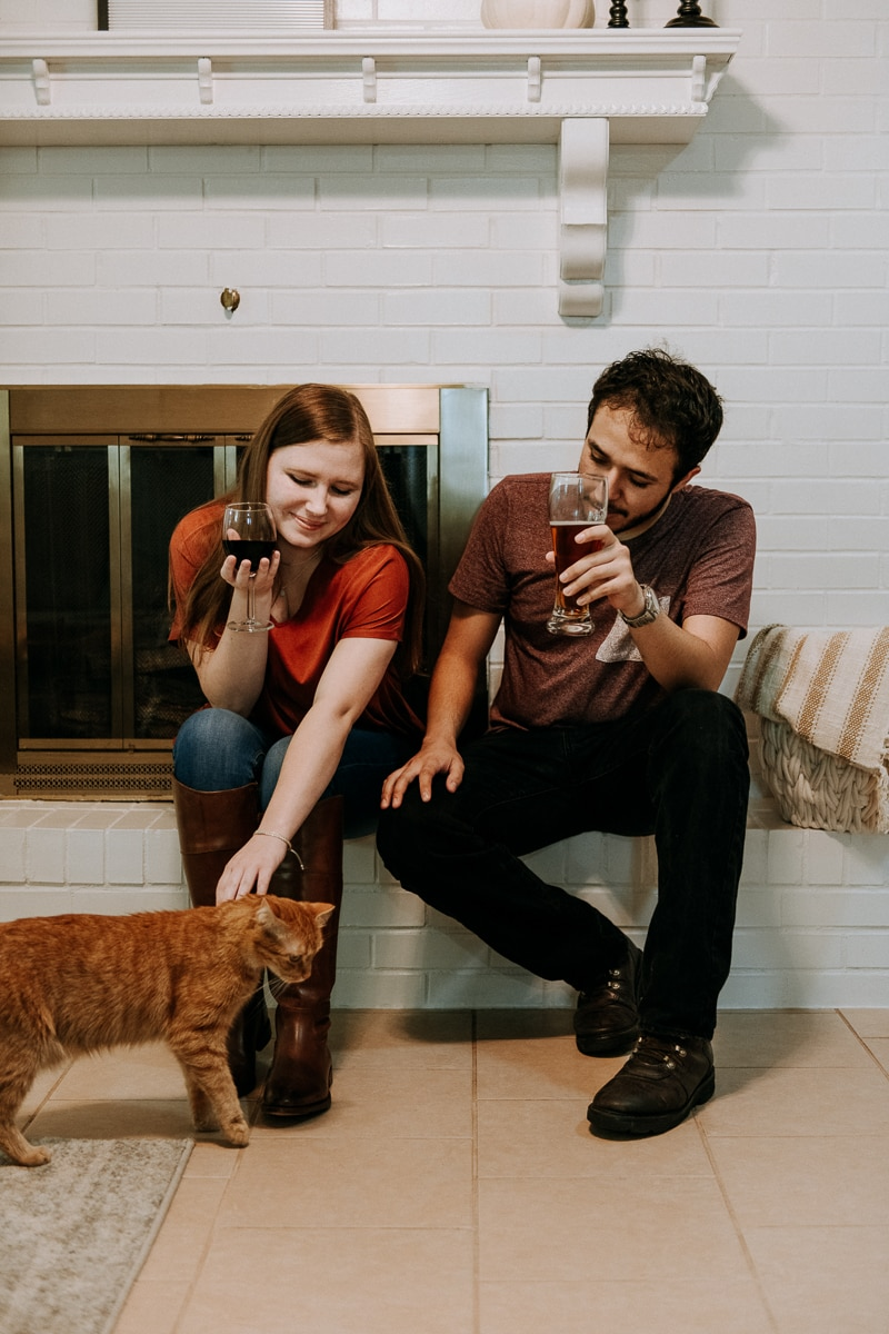 A man and woman sitting by the fireplace petting a cat enjoying Friendsgiving.
