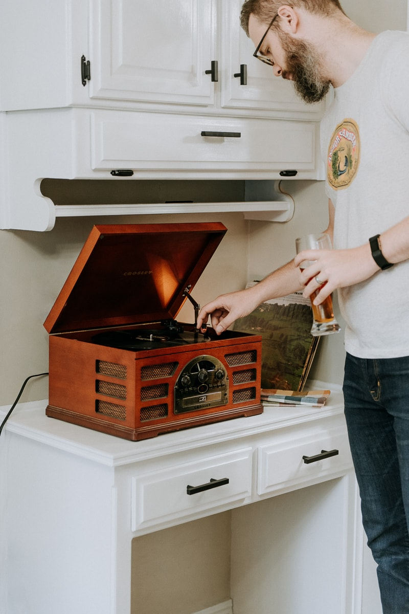 A man putting a record on the record player for Friendsgiving.