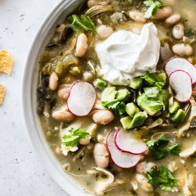 Green chicken chili in a bowl topped with cilantro, radishes, and sour cream.