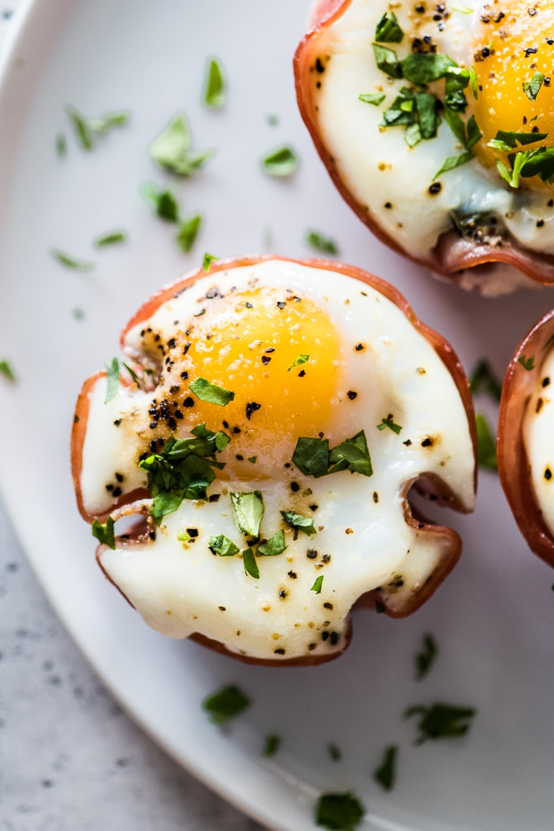 An egg muffin cup on a white plate topped with chopped cilantro.