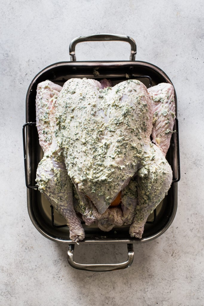 A turkey in a roasting pan covered with herb butter.