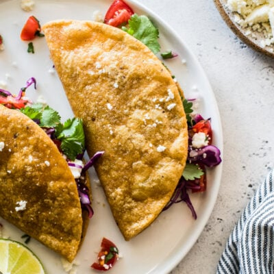 Potato tacos on a white plate stuffed with shredded cabbage and pico de gallo.