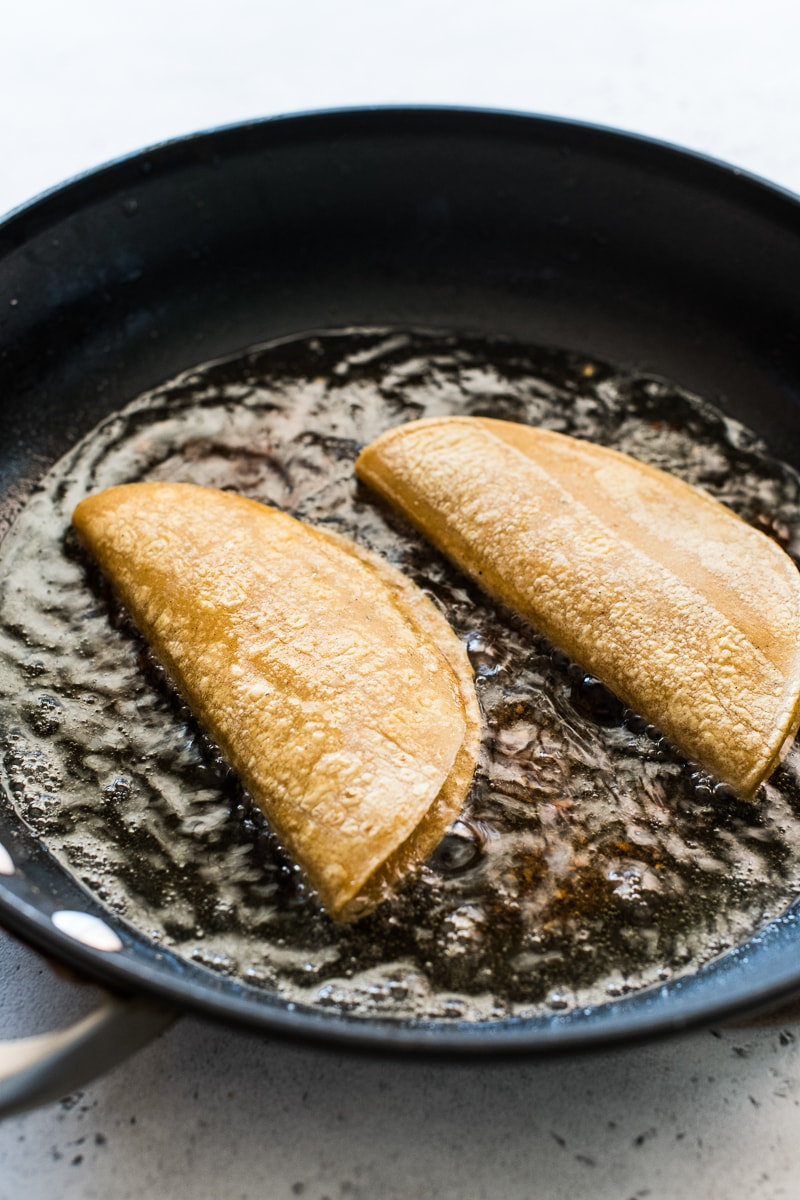 Potato Tacos frying in a large skillet.