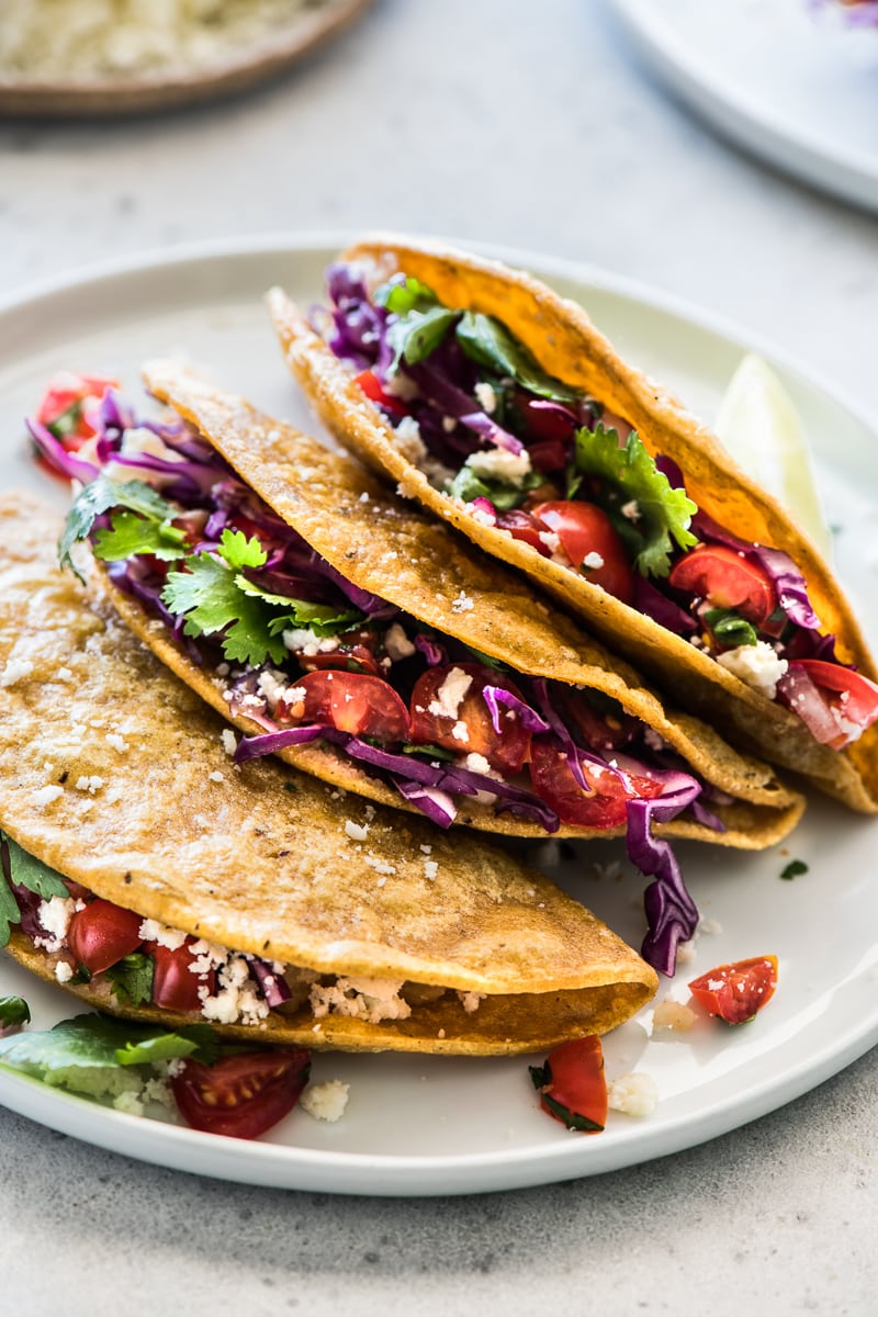 Crispy Potato Tacos filled with shredded cabbage, pico de gallo and cotija cheese.