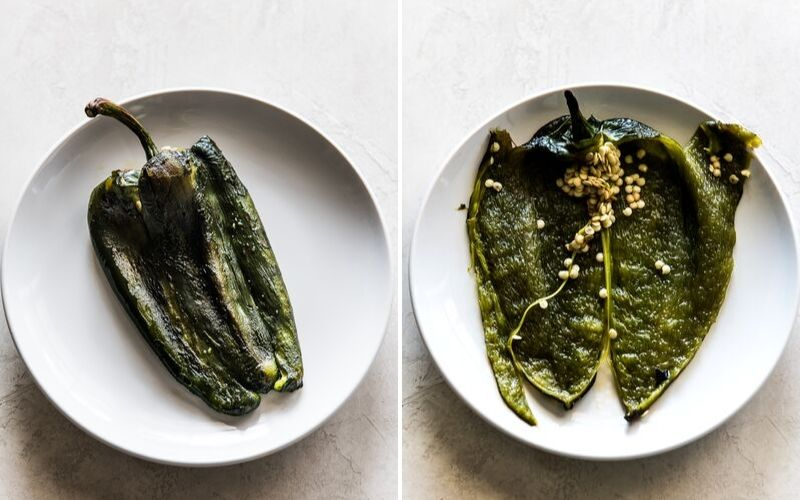 A roasted poblano pepper on a plate sliced open to reveal the seeds.